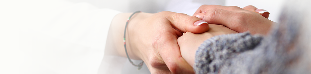 Closeup of caregiver holding hands of another person in a comforting way