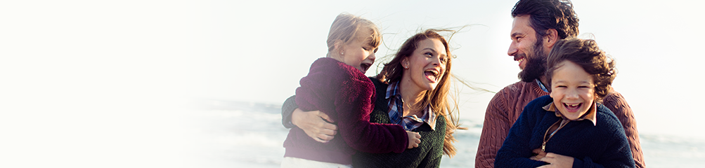 Laughing, happy family on beach with mom and dad carrying kids