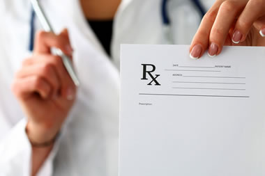 Torso of pharmacist with close-up of their hand holding a prescription pad