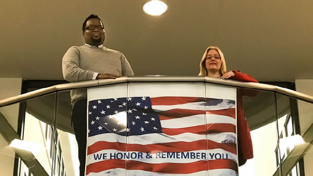 Mareco Smith and Denise Christiansen standing at top of stairs with American flag