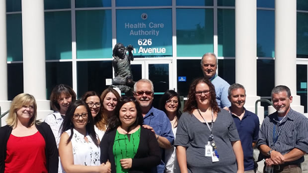 Office of Medicaid Eligibility and Policy (OMEP) staff standing in front of the fountain outside HCA