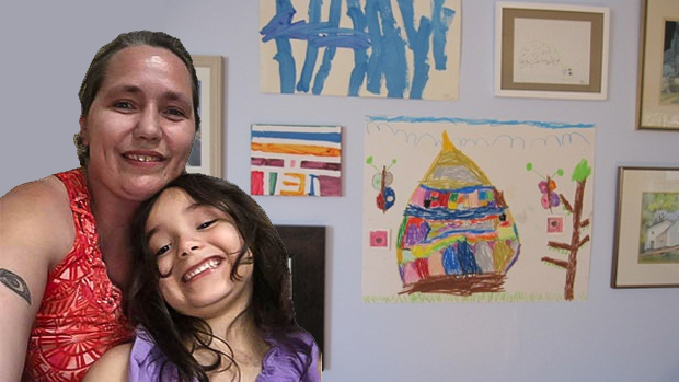 Shayne Tackett and daughter in front of daughter's artwork on the wall