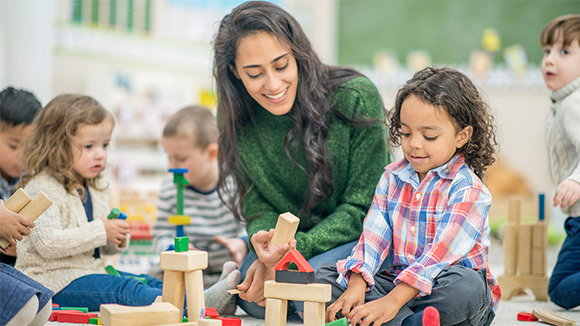 Young female teacher with kids, playing with blocks